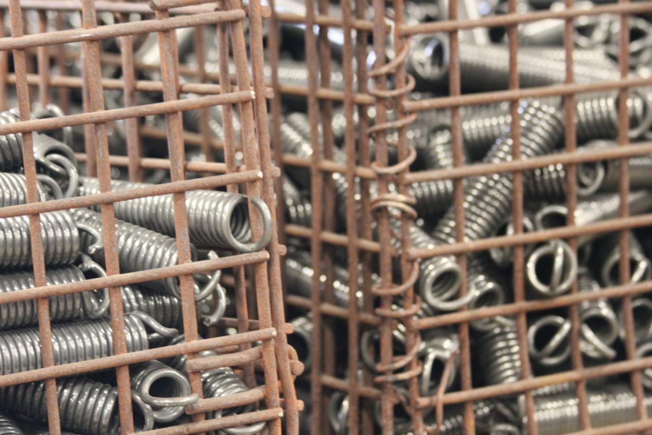 Extension springs collected in a wire form basket.