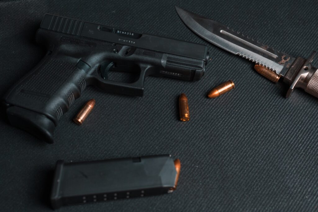 A standard handgun with three bullets out of a magazine on a black table.