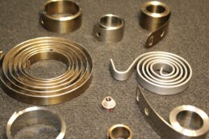 Constant force springs, flatter in shape than standard springs, are economical and easy to assemble.