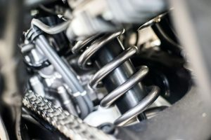 Mid-West Spring & Stamping is one of the leading coil spring manufacturers in the United States. A coiled spring suspension system in a motor vehicle (closeup).